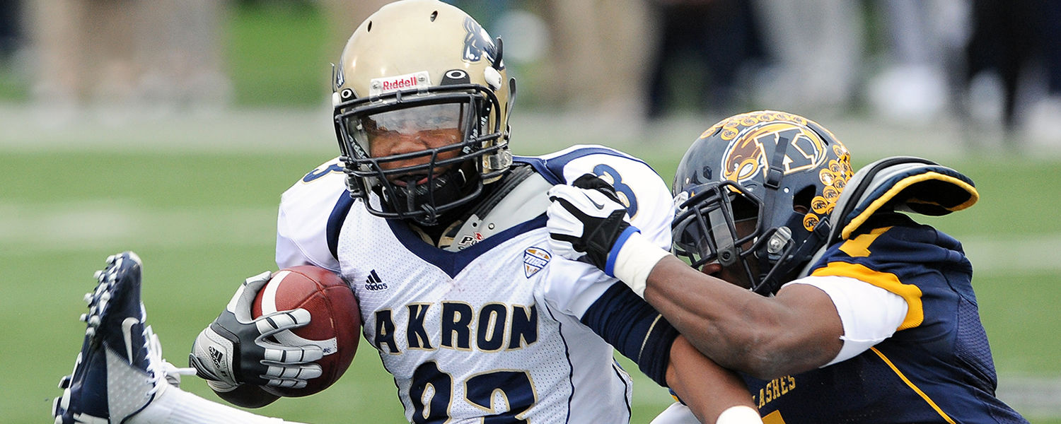 The Kent State defense swarms a University of Akron player during a 35-24 win at Dix Stadium.