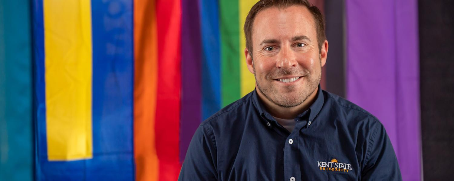 Ken Ditlevson, director of Kent State's LGBTQ+ Center sits in front of flags representing the LGBTQ community.