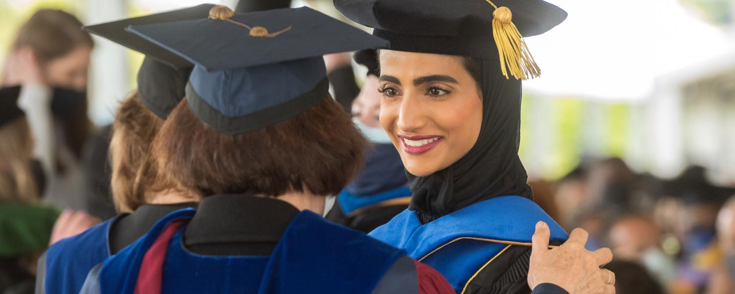A Kent State professor congratulates a Ph.D. graduate before the start of the Advanced Degree Commencement Ceremony.
