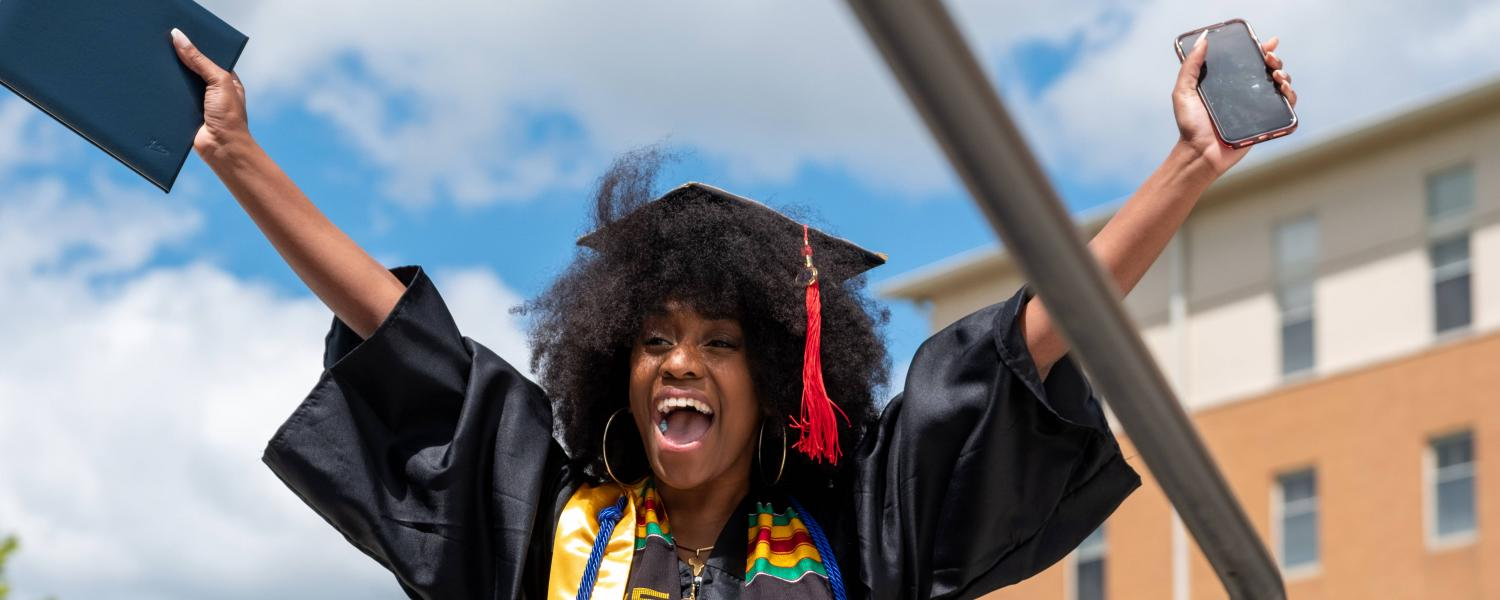 A new Kent State graduate from the College of Communication and Information celebrates after crossing the stage during her commencement ceremony.