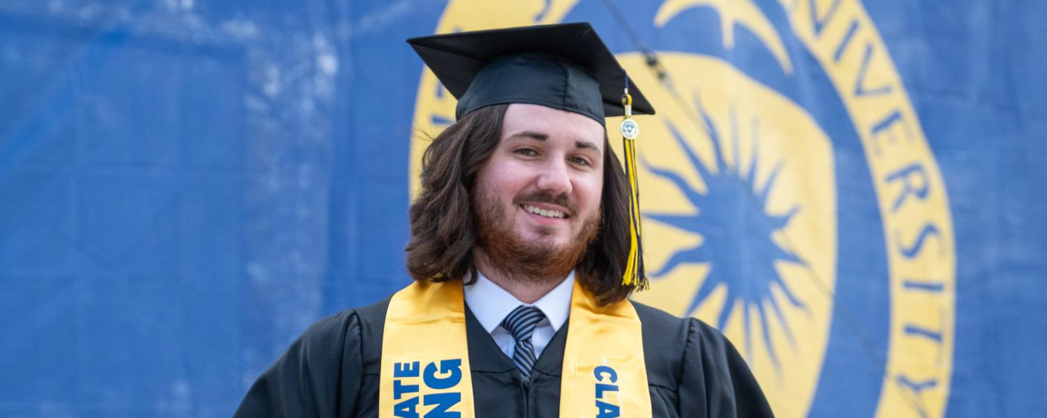 A new Kent State graduate from the College of Communication and Information shows off his diploma during his commencement ceremony.