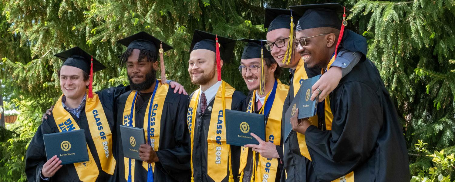 A group of friends smiles for a group photo after their commencement ceremony at Kent State.