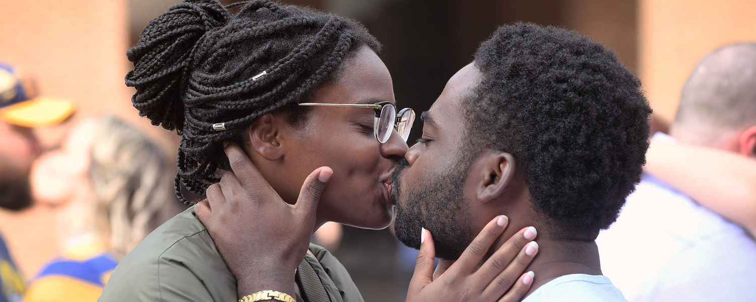 Kent State graduates Lakysha Robinson (left), '17, and Venix Cador, '15, share a kiss during the Alumni Association's Kiss on the K tradition on Risman Plaza. Ms. Robinson is currently a sociology graduate student, and the two are currently engaged.