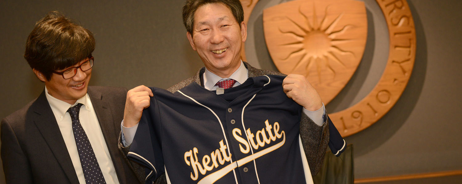 Chang Ho-sung, president of Dankook University in South Korea, shows off the Kent State baseball shirt given to him by Kent State President Beverly Warren after they signed a new agreement that expands the relationship between the two universities.