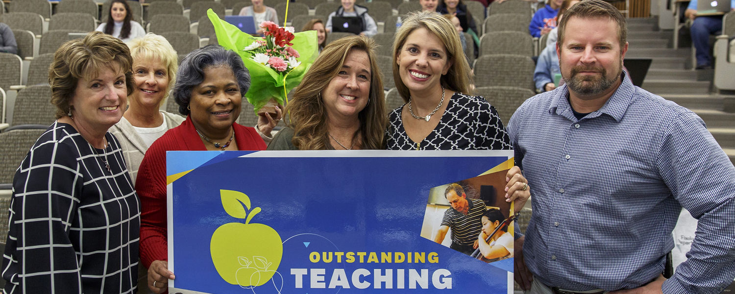 Mary Kutchin (center) recieves her surprise visit from Melissa Dyer and the University Teaching Council