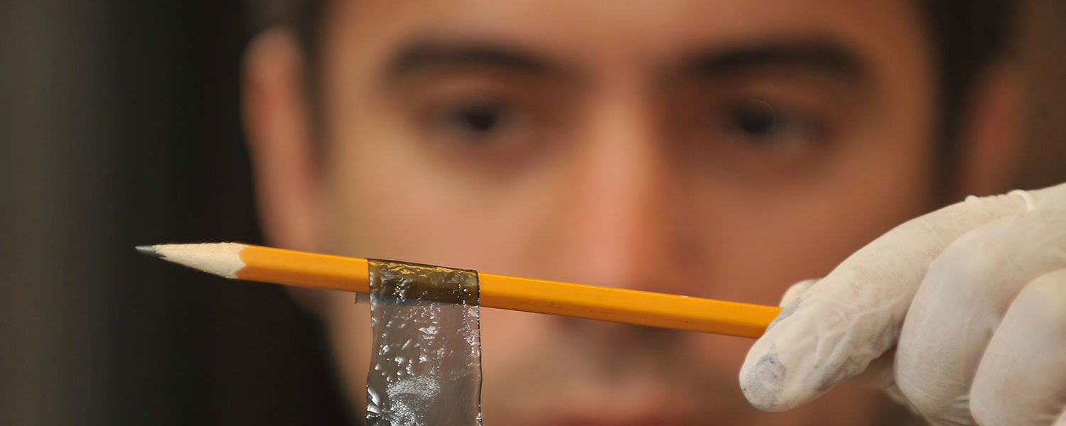 A Kent State graduate student in the Liquid Crystal Institute displays a flexible liquid crystal panel.