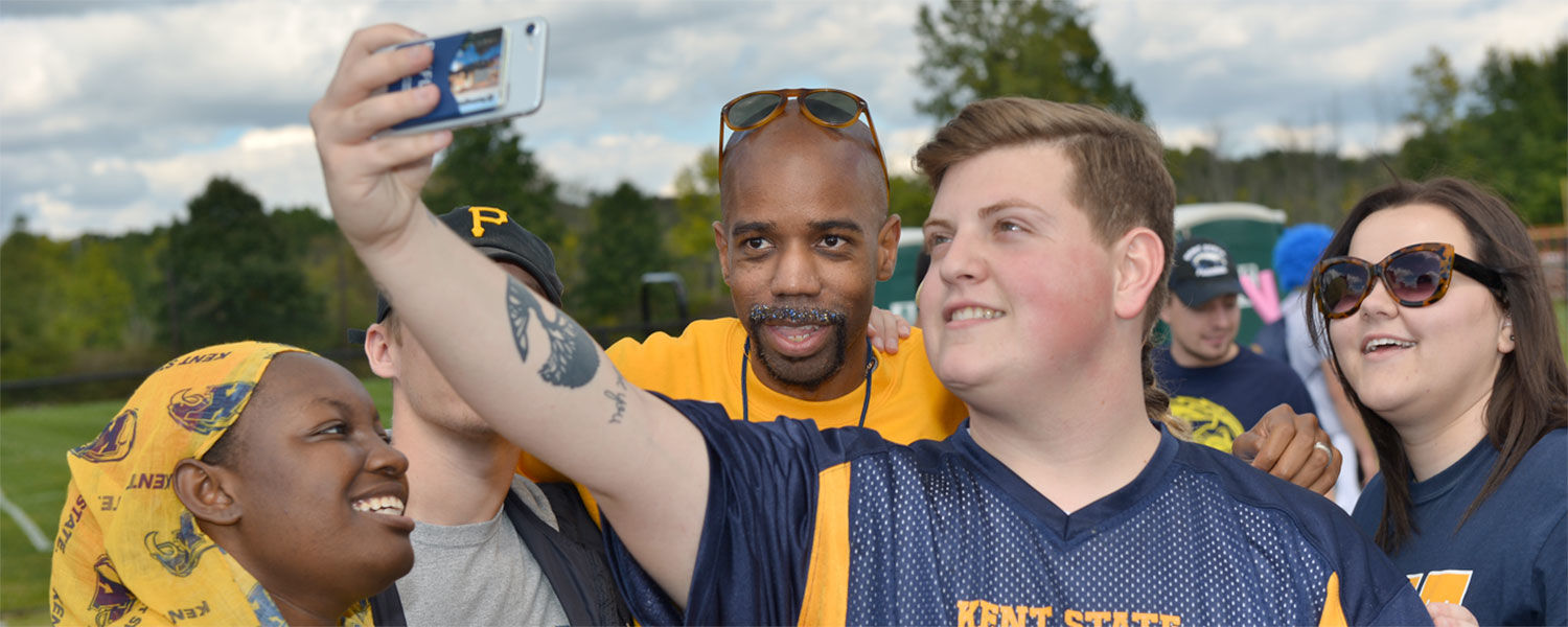 Dr. Lamar Hylton poses for a selfie with students before a Kent State football game.