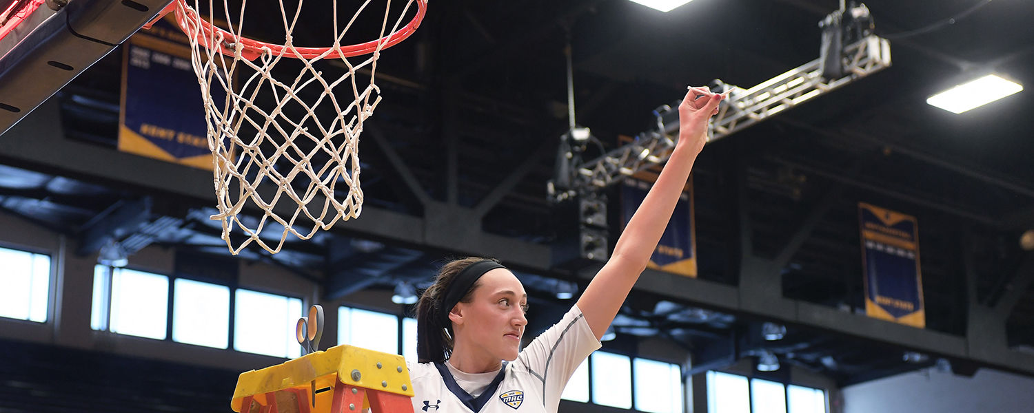 Kent State basketball player Larissa Lurken celebrates the team's championship season by taking part in the tradition of cutting down the net following the final home game in the MAC Center.