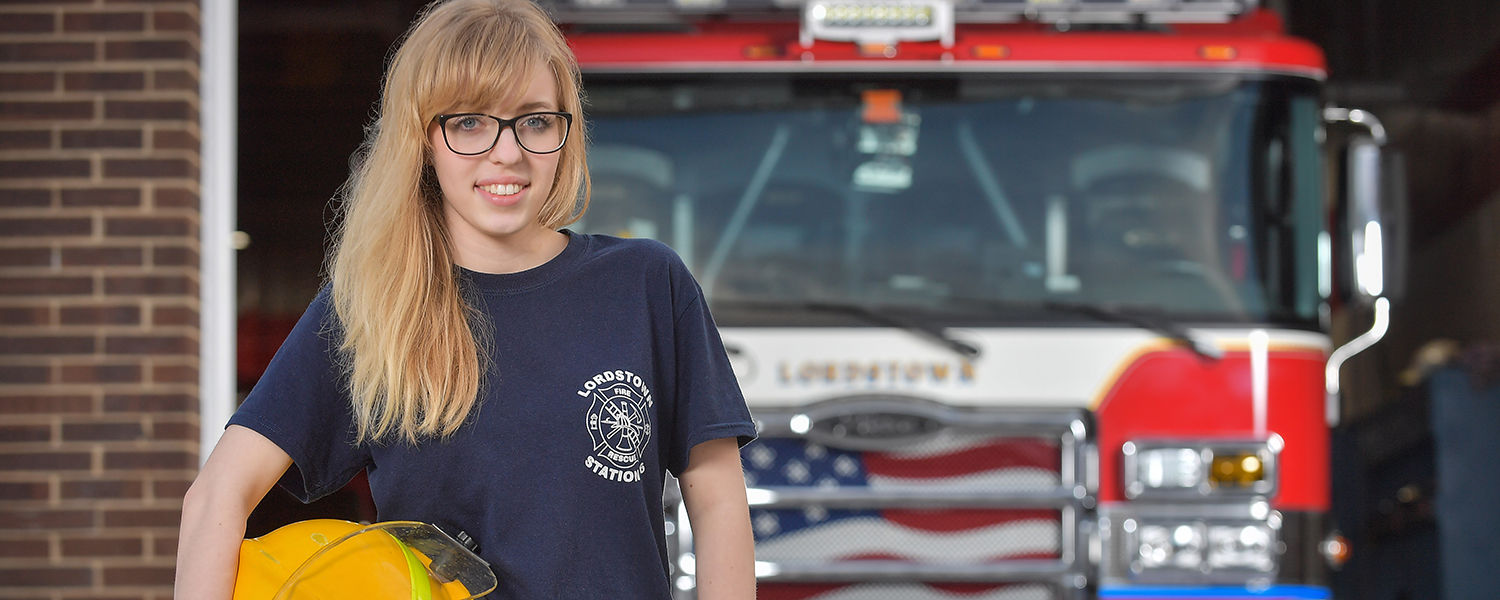 Kent State student Brooke Mullins stands in front of the Lordstown Fire Department – Station 36 in the Village of Lordstown, Ohio, where she serves as a volunteer firefighter.