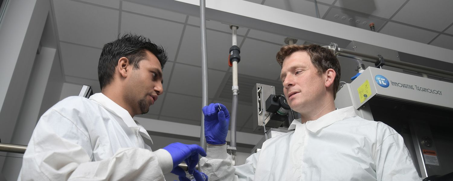 Kent State University Assistant Professor of Physics Björn Lüssem, Ph.D., (right) works with a graduate student (left) in a lab at the Integrated Sciences Building.
