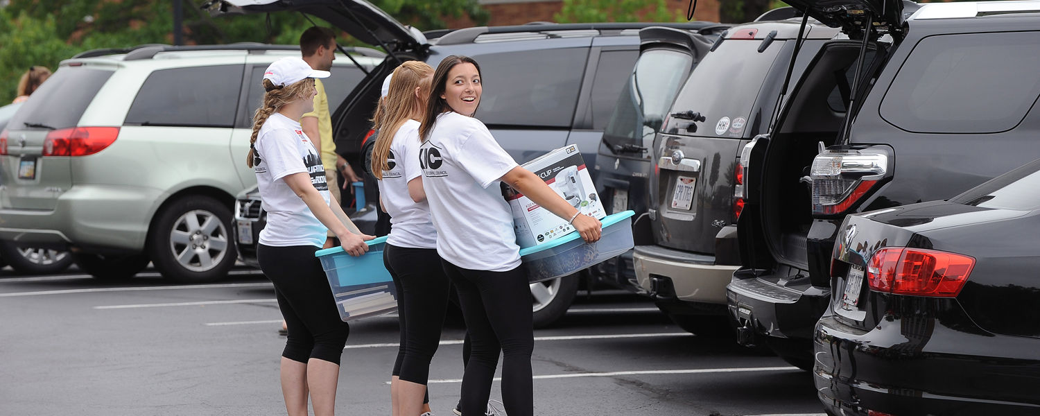 Volunteers line up to assist incoming freshmen near Korb Hall during move-in day on campus.