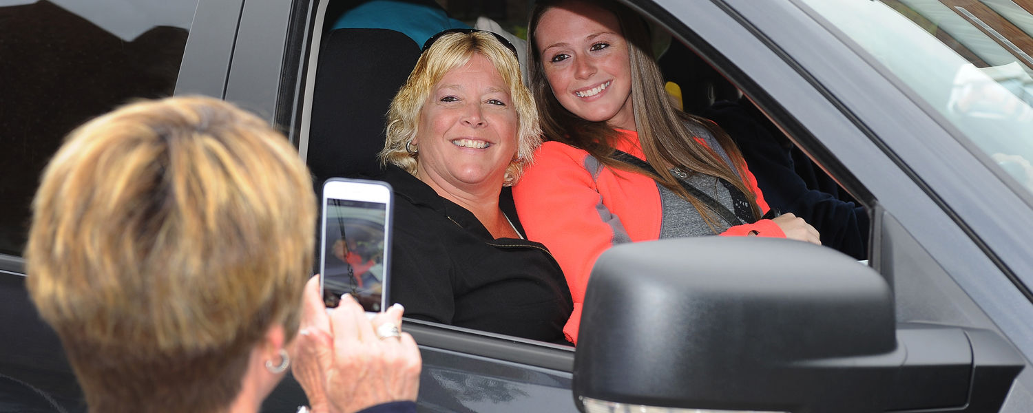 Kent State President Beverly Warren can't resist taking a photo of a freshman student who pulled onto campus seated on her mother's lap because their car was packed too full of personal items for move-in day.