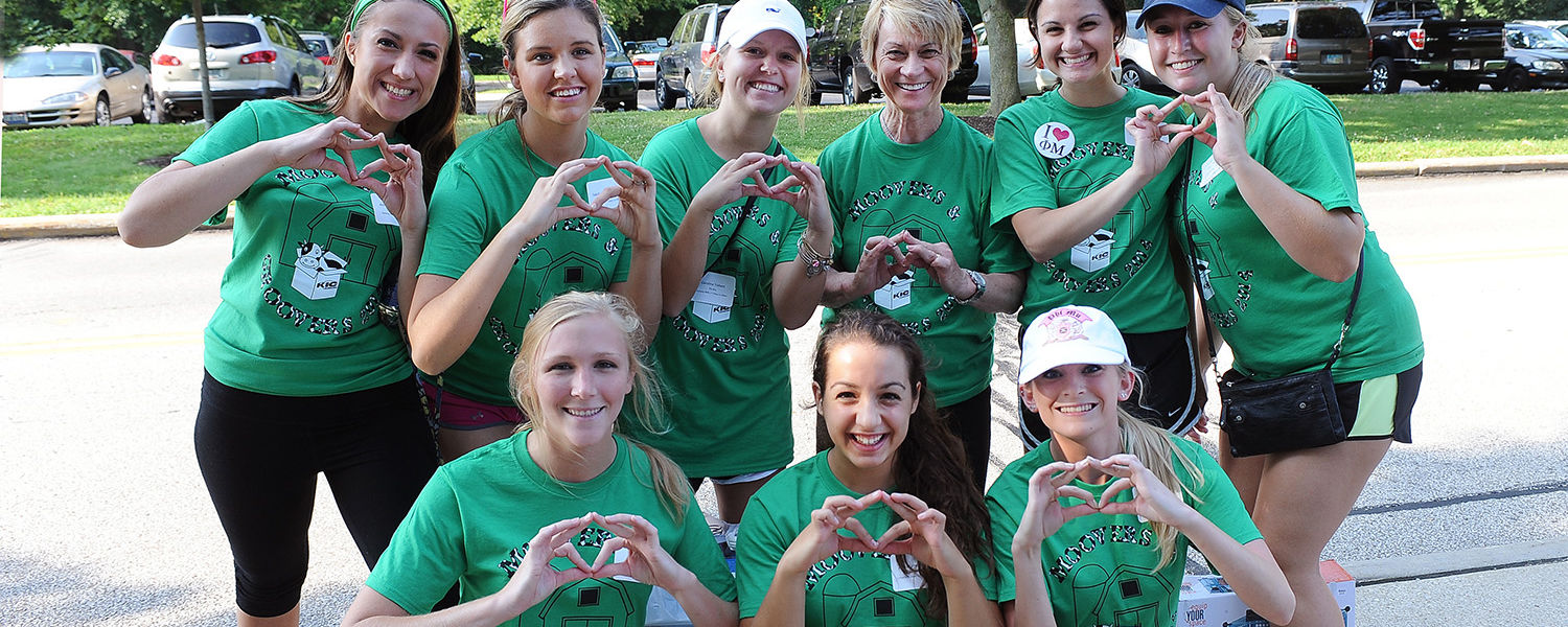 Kent State President Beverly Warren displays her best sorority hand sign while joining sorority volunteers working with the Movers and Groovers program on freshman move-in day.