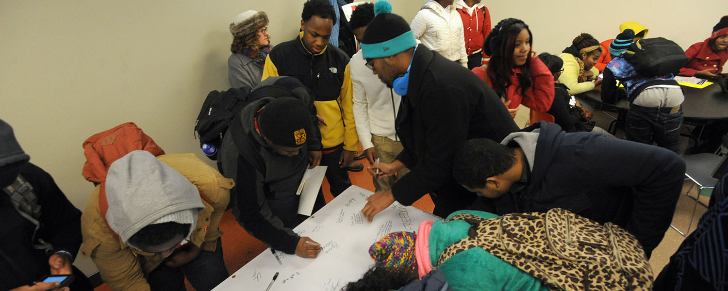 Kent State students sign a banner at Ritchie Hall during the 2014 Martin Luther King Jr. Celebration.
