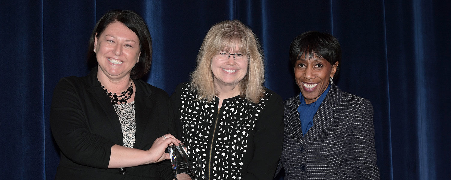 Dana Lawless-Andric (left) and Vice President Alfreda Brown (right) present Amy Reynolds, Ph.D., dean of the College of Communication and Information, with the 2018 Unity Award for Diversity. Dean Reynolds accepted the award on behalf of the college.