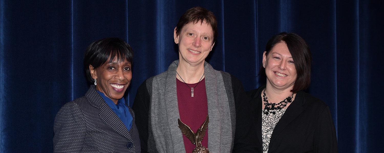 Vice President Alfreda Brown (left) and Dana Lawless-Andric (right) present the 2018 Diversity Trailblazer Award to Kathy Wilson, Ph.D., professor of economics.
