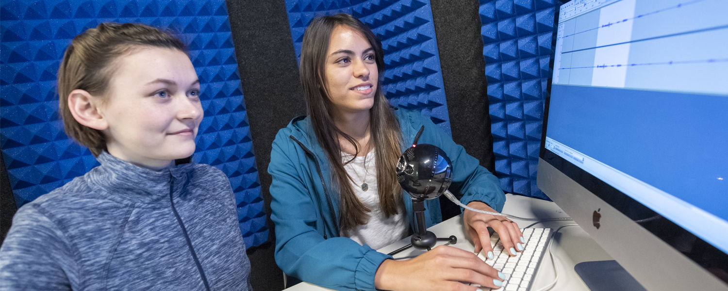 Two Kent State students collaborate on an audio recording in the Student Multimedia Studio