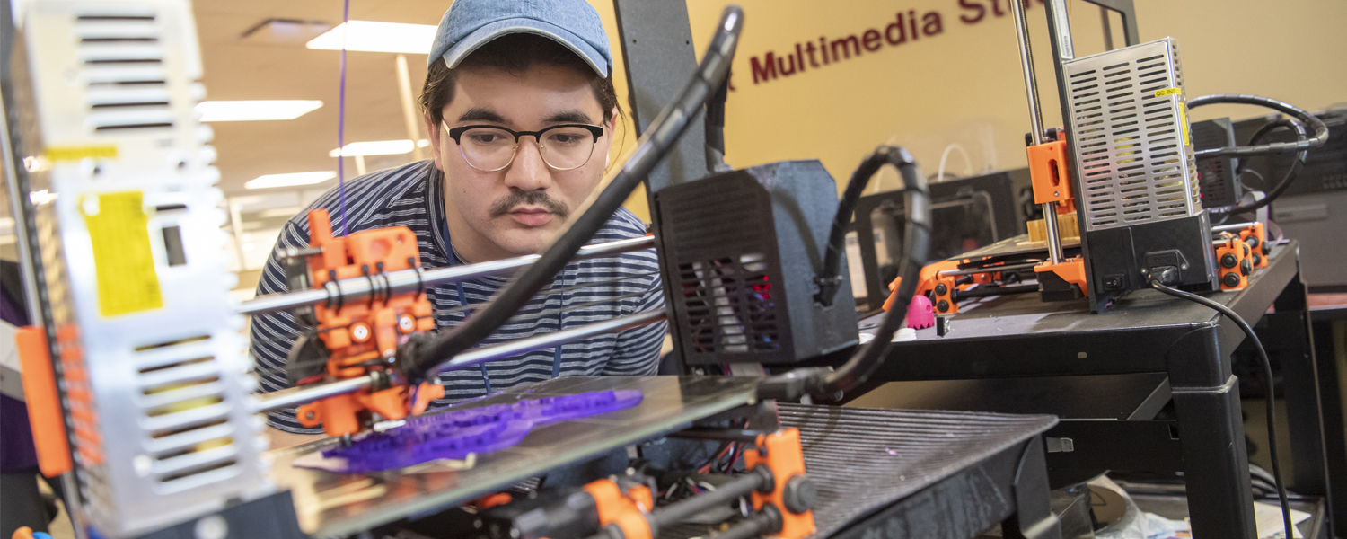 A student produces a class assignment on the 3D printer in the student multimedia studio