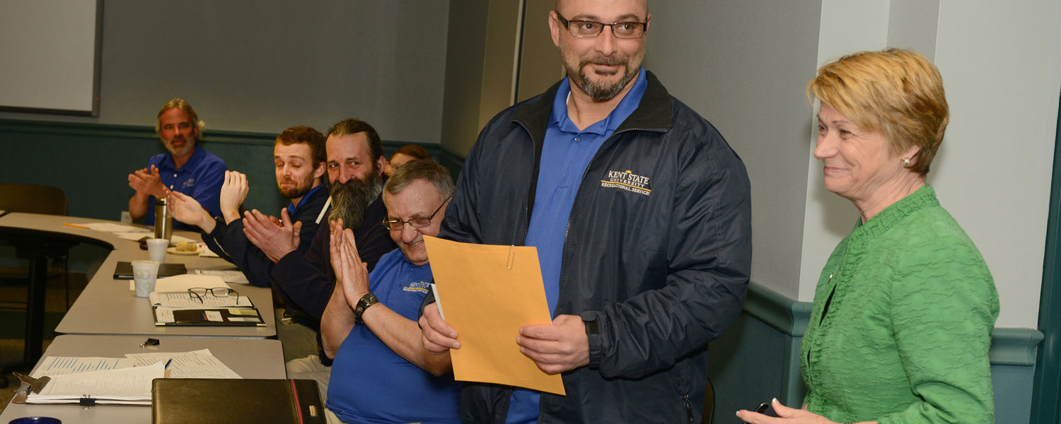 Kent State President Beverly Warren interrupts a staff meeting to give Scott Manzo a President's Excellence Award.
