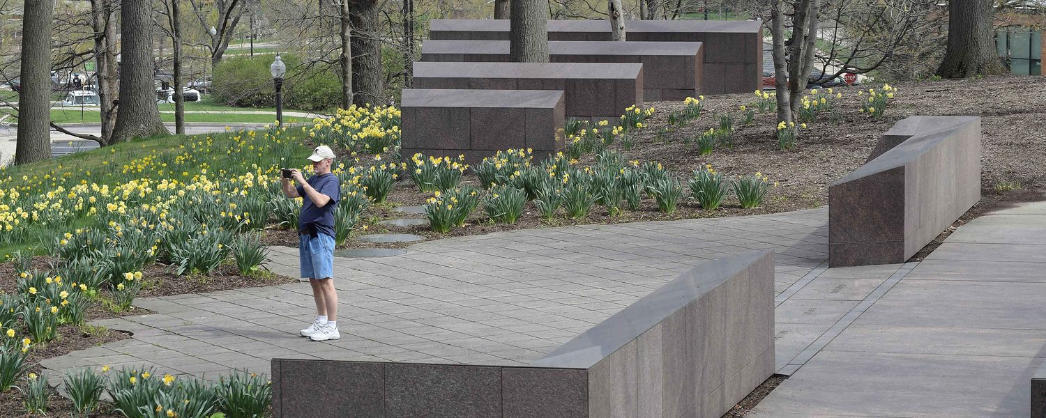 A visitor to the Kent State campus takes photos at the May 4 Memorial prior to the start of the annual May 4 Commemoration, held this year in the Kent Student Center Ballroom.