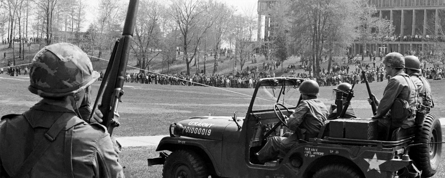 National Guard personnel and vehicle in foreground, crowd gathered by Taylor Hall in background