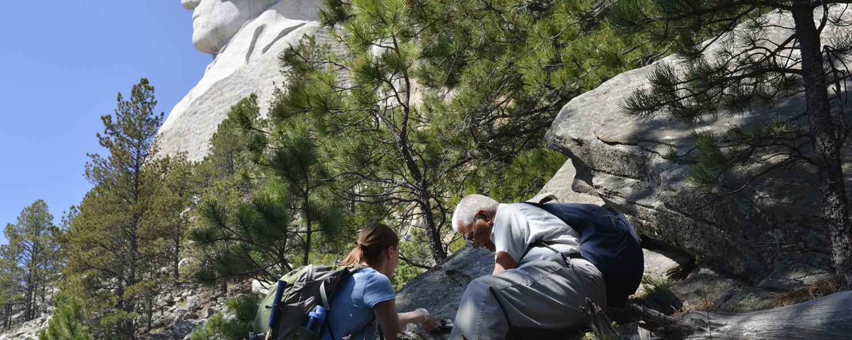 Kent State University graduate student Lindsay Poluga and Professor of Geology Abdul Shakoor use the Brunton compass to take discontinuity measurements at Mount Rushmore. (Photo credit: Eric Bilderback)