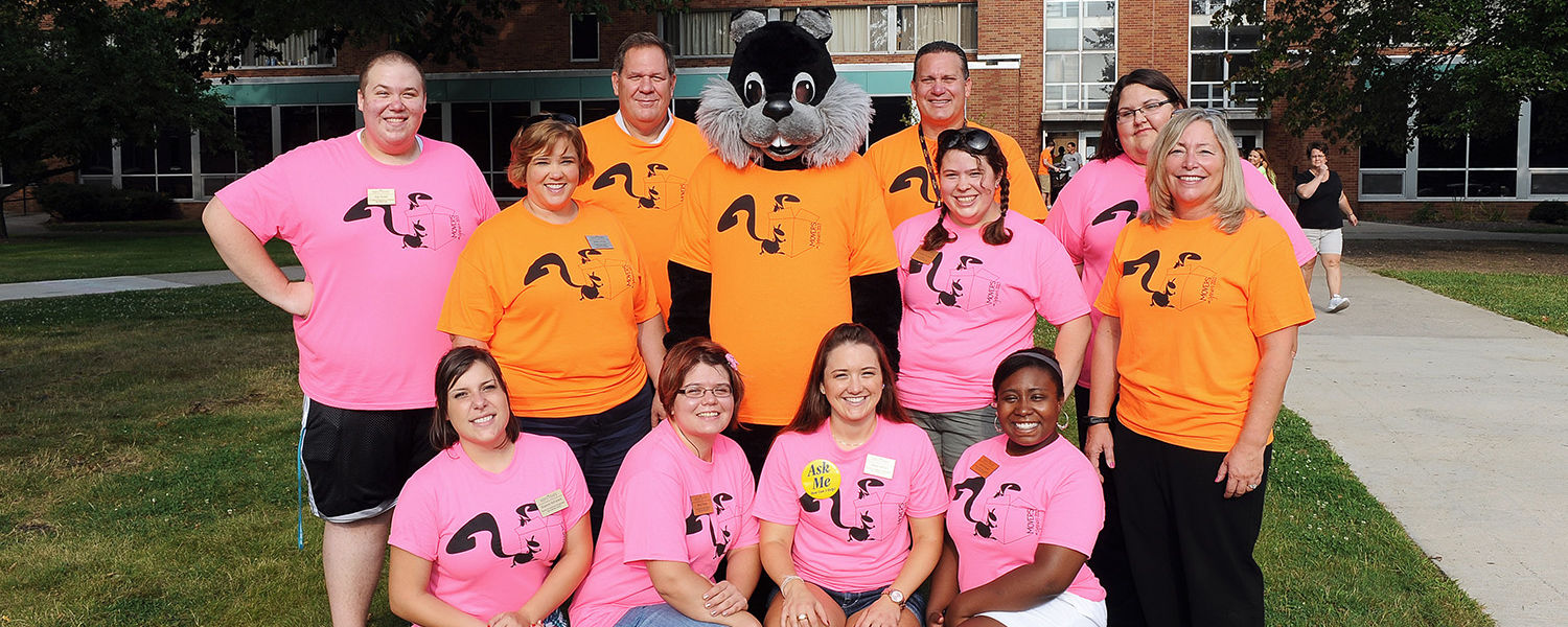 Kent State executive officers, students and Skip, the black squirrel, wait  for a new round of incoming freshmen during move-in day at the residence halls.