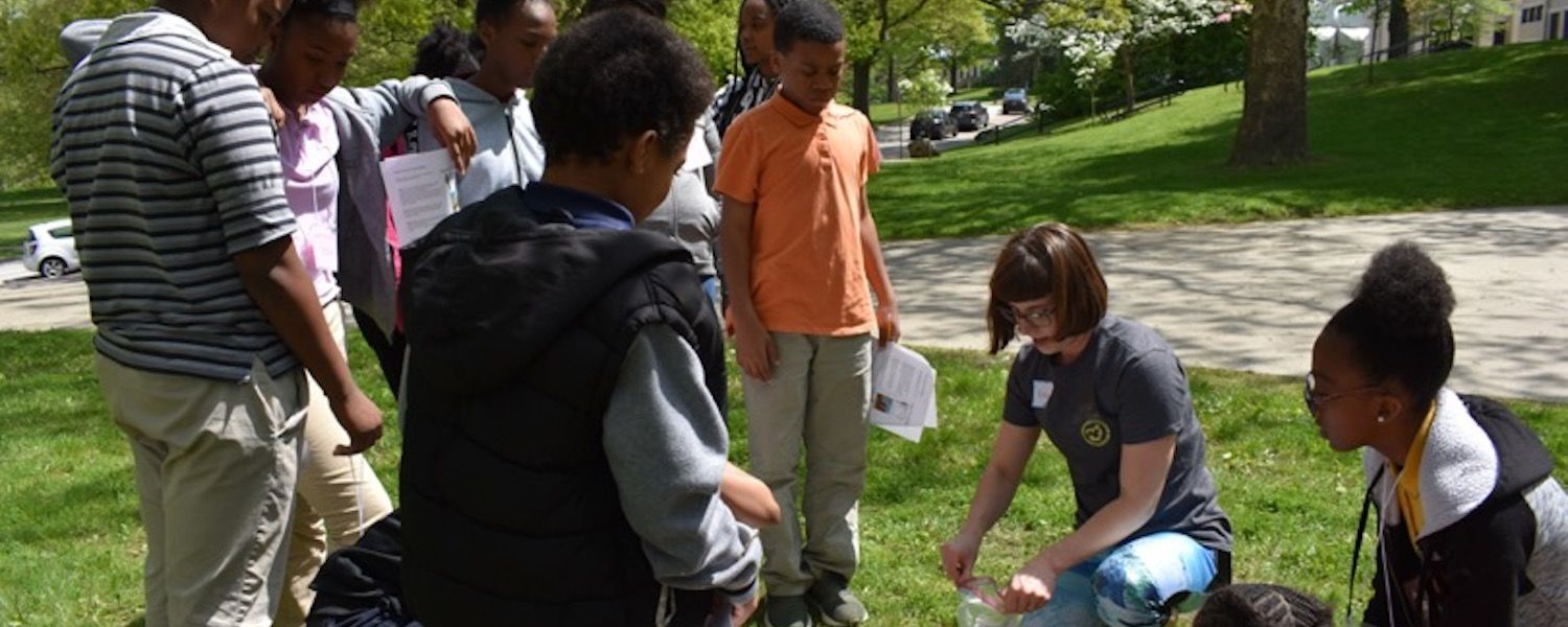 Kent State department of Geology graduate student Kortney Cole shows Schumacher Elementary sixth grader students how to collect soil samples.