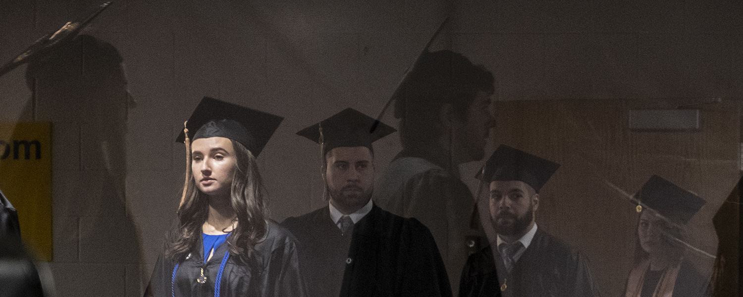 Kent State graduates are reflected in a window of the MAC Center as they file in for their Commencement ceremony.