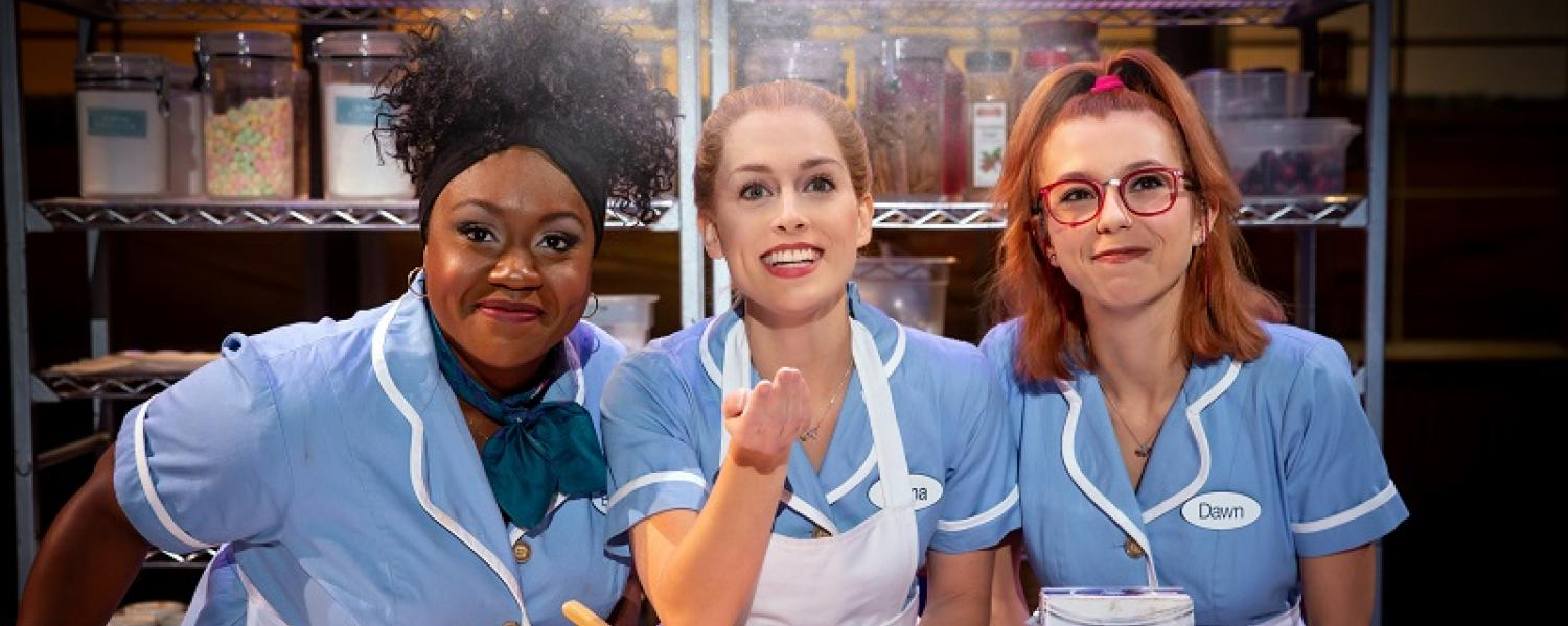 picture of three cast members of National Tour of Waitress wearing uniforms in a kitchen standing behind a table of baking items