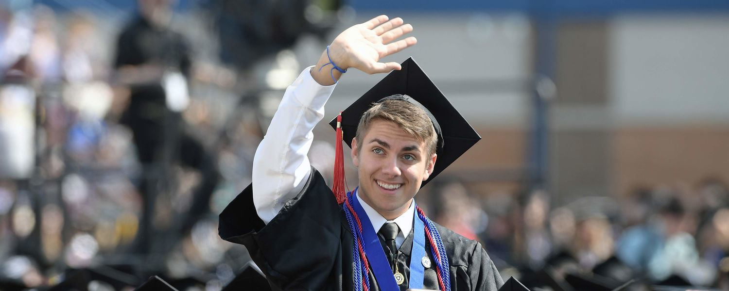 School of Communication Studies alumnus Nicholas Peters waves to his parents as he walks across the stage at graduation. (photo by University Communications and Marketing)