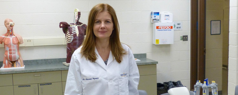 Dr. Daniela Popescu, M.D., Ph.D standing in classroom