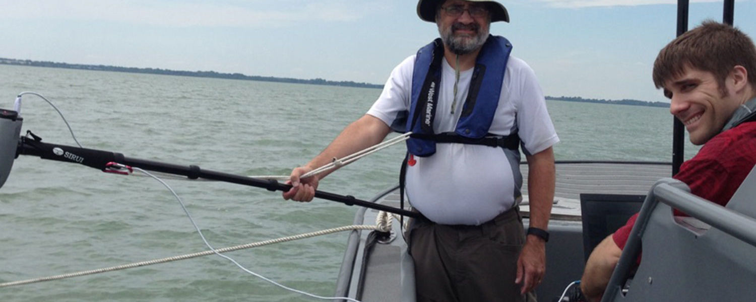 Kent State Geology Professor Joseph Ortiz, Ph.D., and undergraduate student Andrew Congdon take a few moments between collecting measurements of surface reflectance in Sandusky Bay. (Photo credit: Sunny Dickerson, Bowling Green State University)