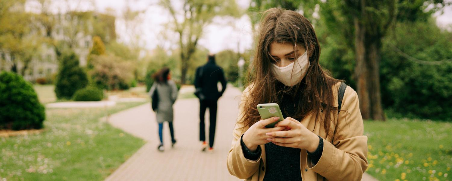 Young women with mask on cell phone, Photo by Maksim Goncharenok from Pexels
