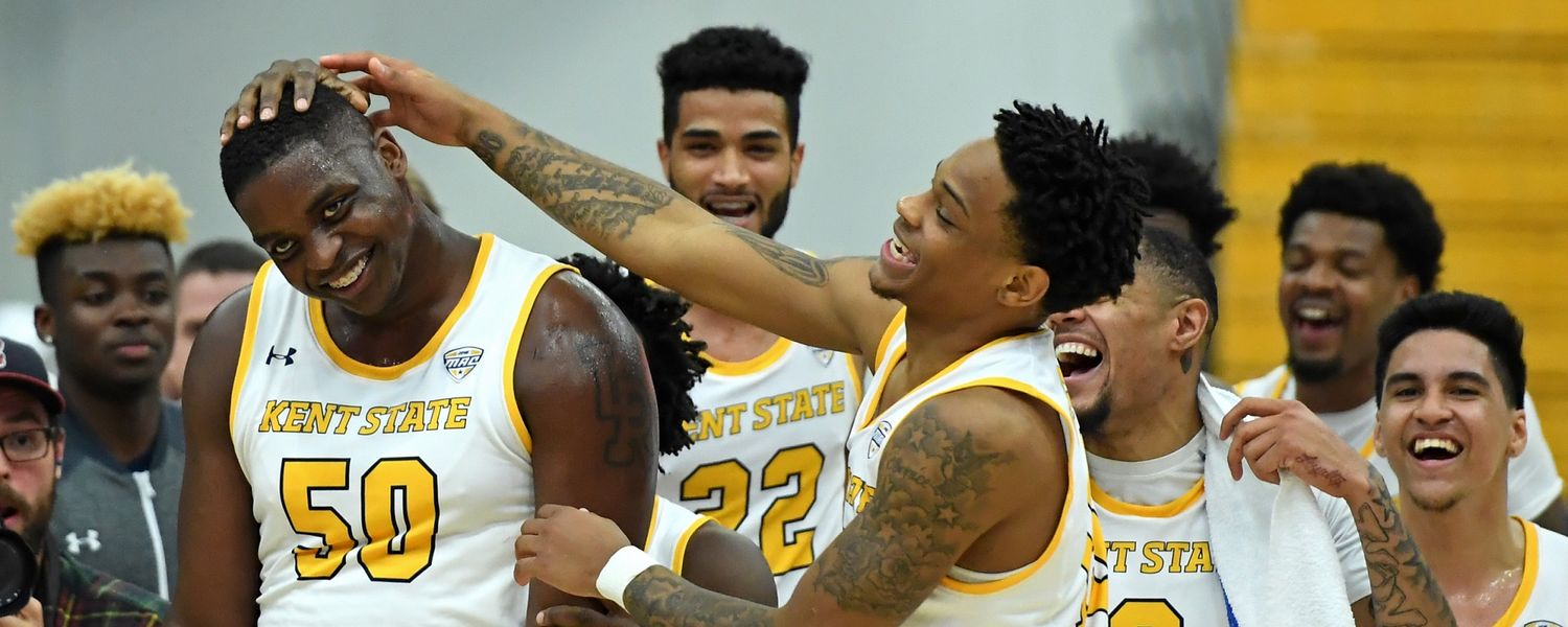 Kalin Bennett (left) is congratulated by his teammates for playing in his first college basketball game.