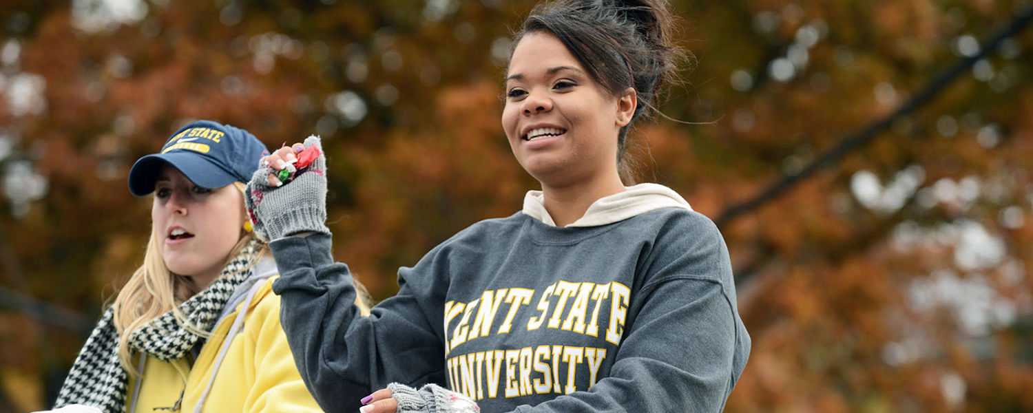 Kent State students in the Homecoming Parade throw candy to attendees along the parade route.
