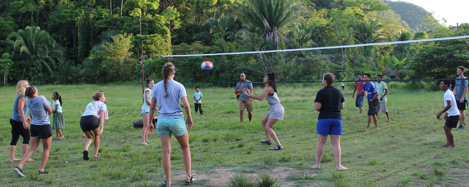 Kent State student-athletes play volleyball with local children in Aguacate, Belize.
