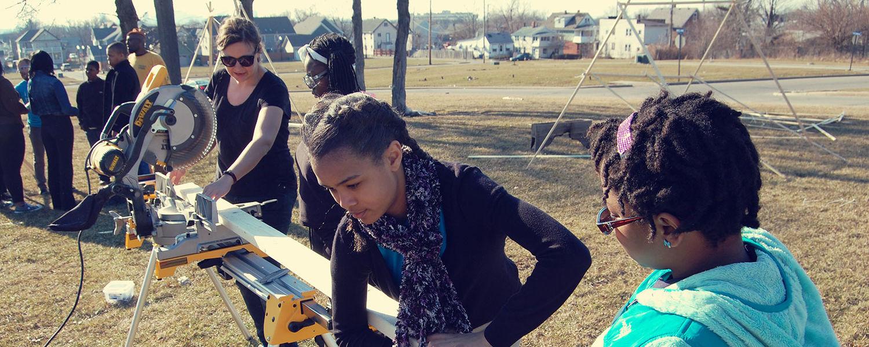 Kristen Zeiber (far left) of Kent State's Cleveland Urban Design Collaborative leads students through a fabrication workshop in Cleveland's Buckeye neighborhood.