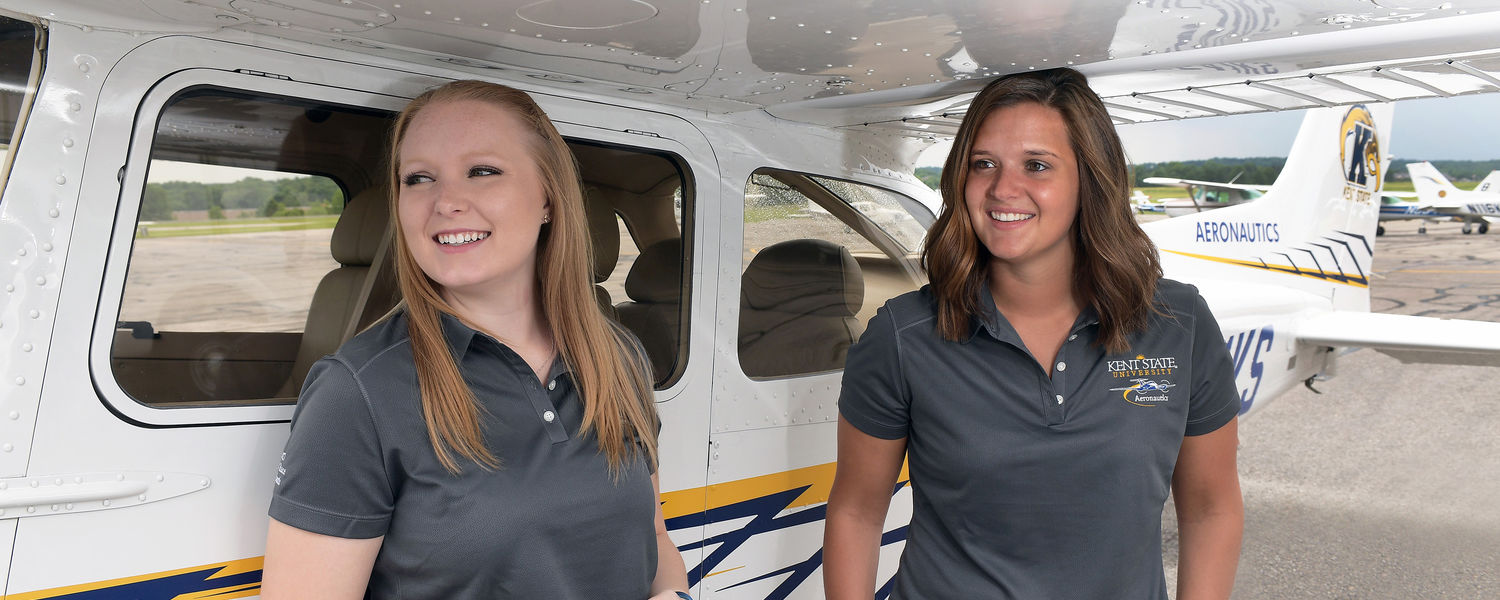 Helen Miller (left) and Jaila Manga discuss their race strategy during a rain shower a day prior to departing from the Kent State University Airport for the Air Race Classic.