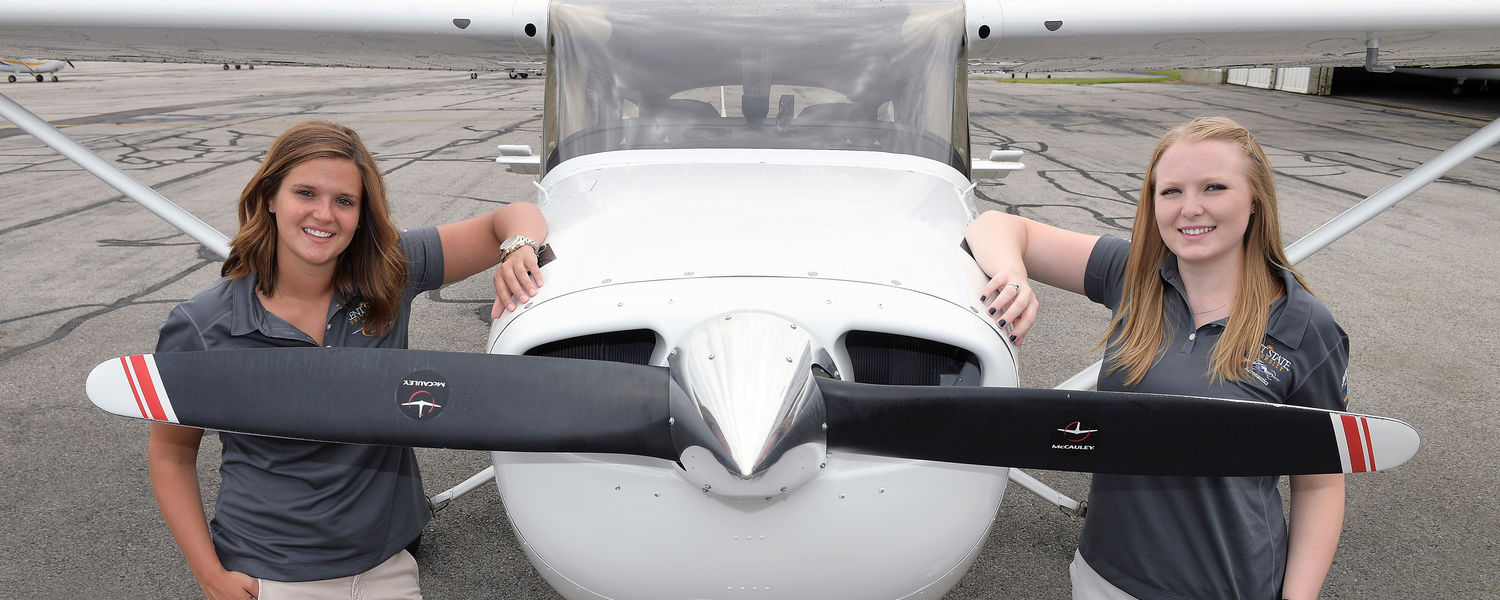 Jaila Manga (left) and Helen Miller pose near the propeller of their Cessna Sky Hawk at the Kent State University Airport, preparing their plane for the 41st Air Race Classic.