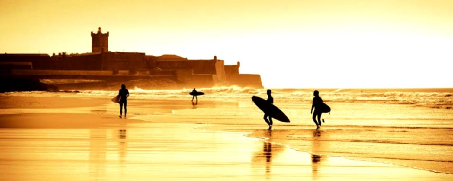 Image of sunset on a Portuguese beach with surfers near water. Peaceful and serene.
