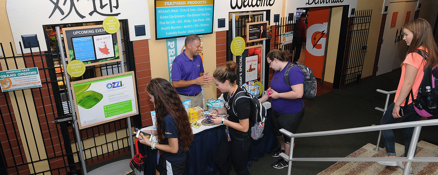 Students stop by a vendor table for free samples at the entrance to the Prentice Café during the grand opening of the gluten free dining hall on the campus of Kent State University.