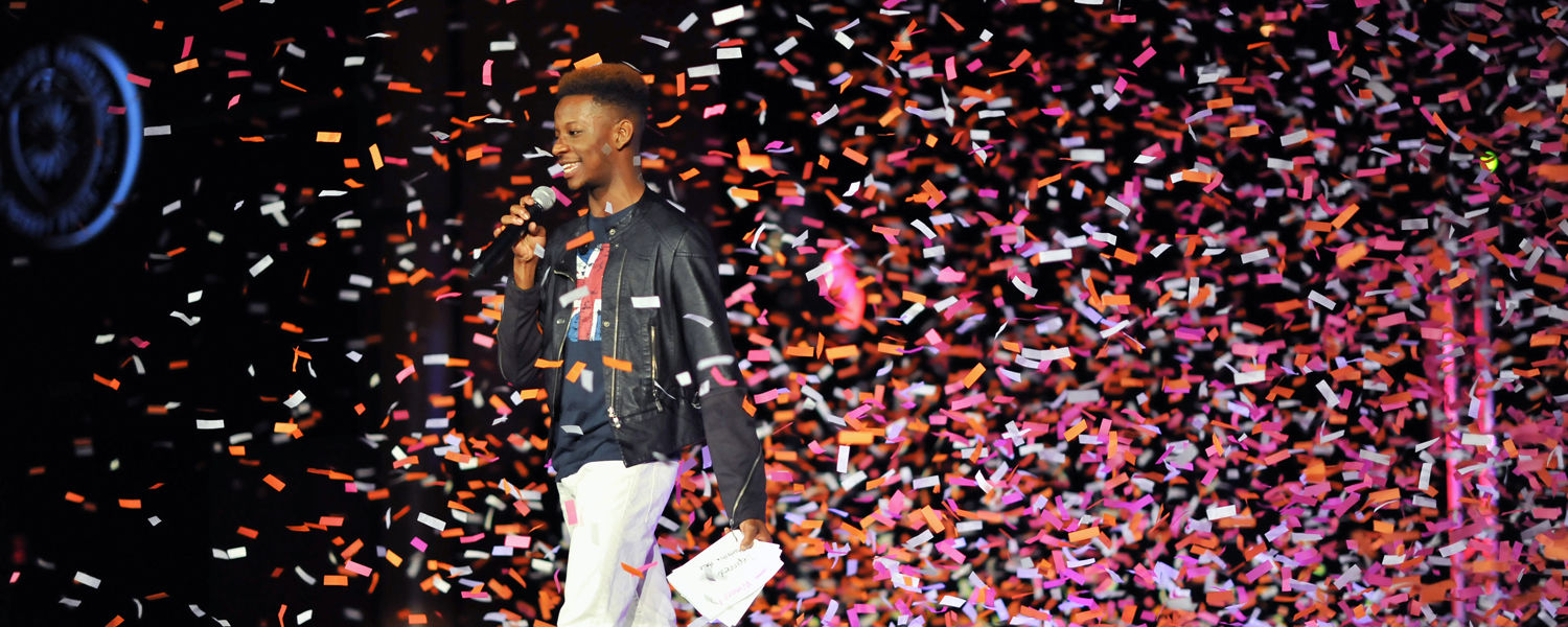 Steffahn Maclin, last year's Rock the Runway emcee, addresses the audience as confetti falls onto the runway. (Photo credit: Thomas Farmer Photography)