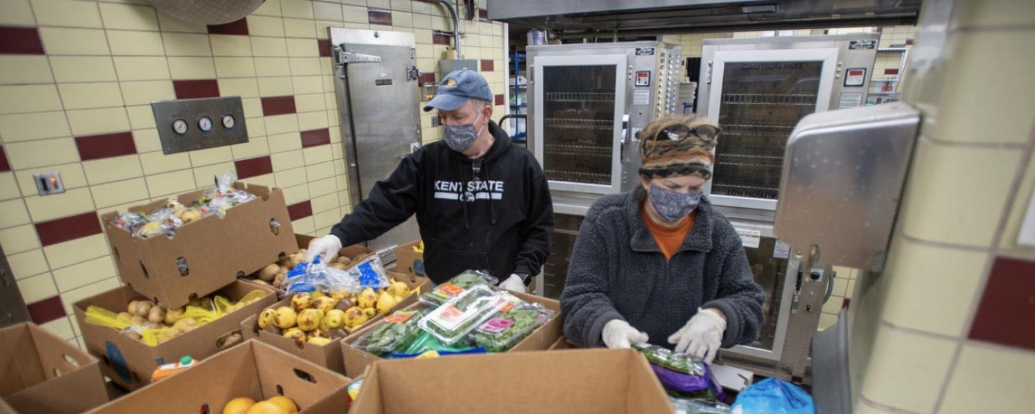 Volunteers Dave and Terri Cardy pack and weigh produce to hand out at the Campus Kitchen in Beall Hall.
