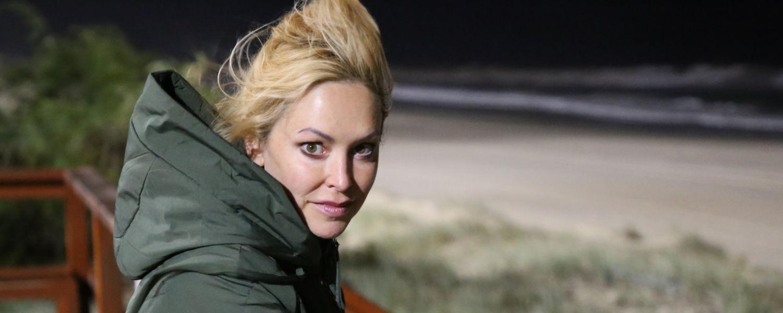 Rachel Armstrong, of Newcastle University (U.K.) stands near a beach at night.