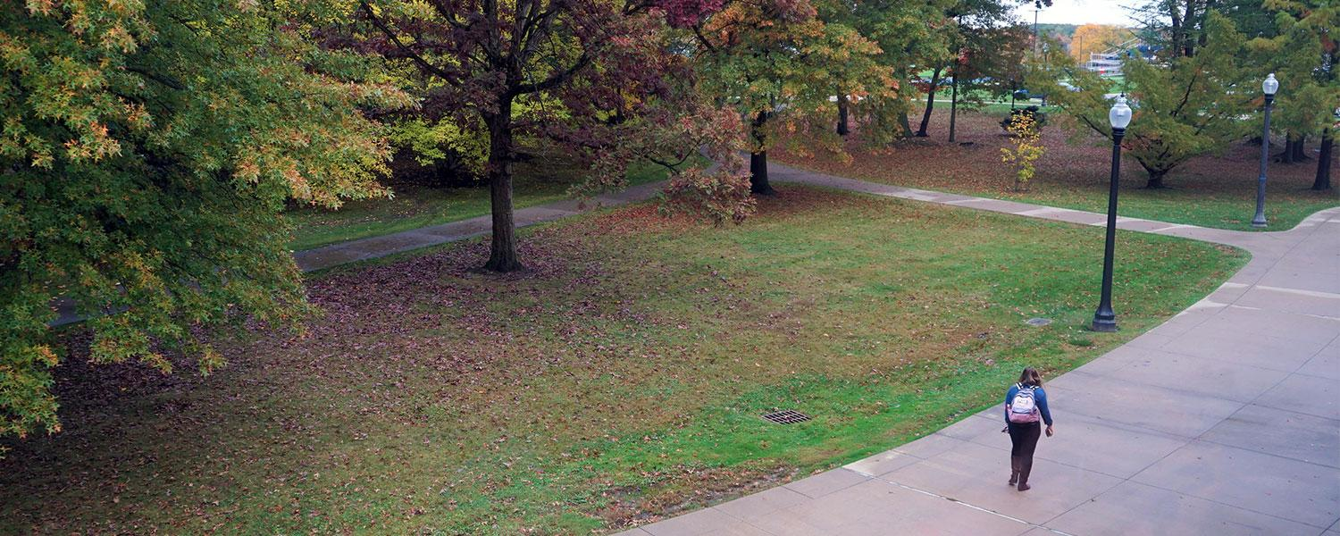 A student walking behind Henderson Hall during the fall semester.