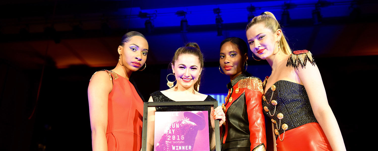 Surrounded by her models, an emotional Kelly Neiser (second from left), who hand set more than 3,200 rhinestones for her winning collection, shows off her Rock the Runway award. (Photo credit: Thomas Farmer Photography)