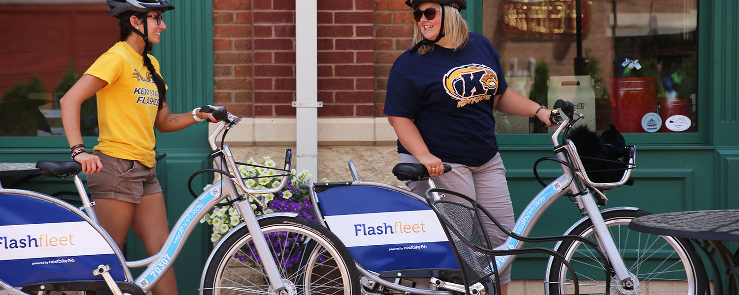 Two Kent State University students ride Flashfleet bikes in downtown Kent. Kent State was named a Green College in the 2016 Princeton Review Guide to 361 Colleges for its focus on environmentally friendly transportation.
