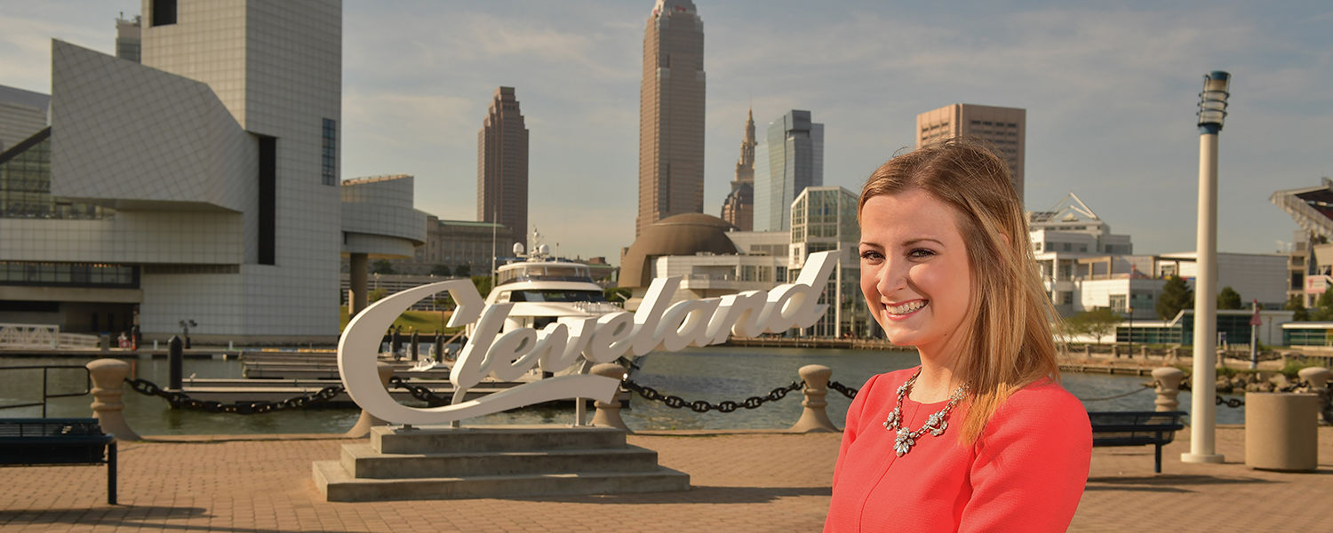 Kent State public relations major Sarah Matthews stands near the Cleveland script sign at North Coast Harbor's Voinovich Park with the city in the background. She is one of several Kent State students involved in the 2016 Republican National Convention.