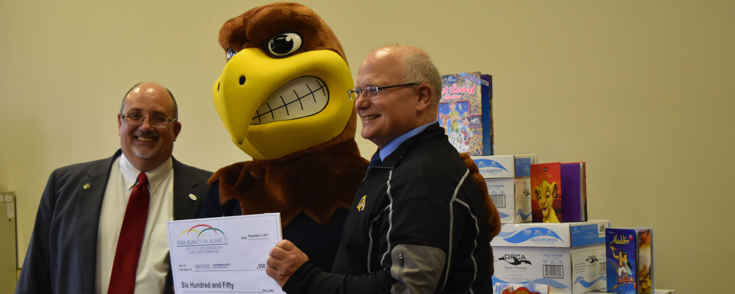 Joe Rossi, CEO of the Area Agency on Aging 11, presented a check and hundreds of books to Dean David Dees – and Flash.